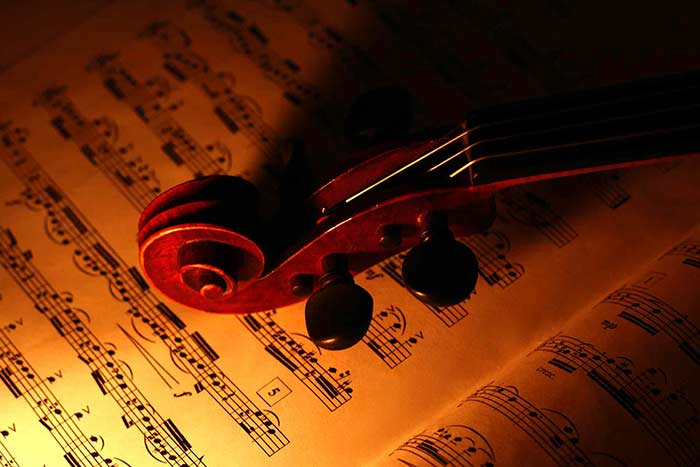 violin on a music sheet with dramatic lighting feat