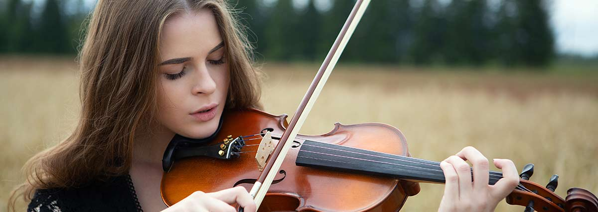 woman playing the violin outdoors